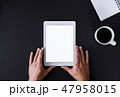 A top view of male hands holding tablet on a desk. Copy space. 47958015