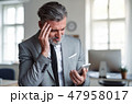 A frustrated businessman with smartphone standing in an office, reading bad news. 47958017