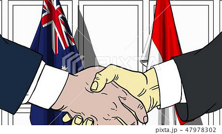 Businessmen or politicians shaking hands against flags of Australia and Indonesia. Meeting or 47978302