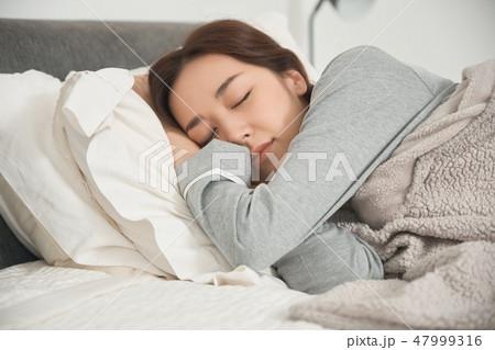 ベッドで寝ている女性 47999316