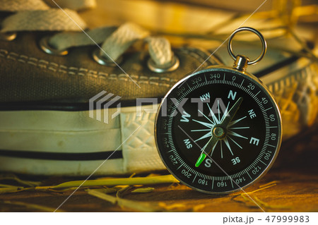 Compass and sneakers with dry wheat straw. 47999983