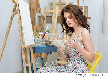 woman with easel, palette and brush painting at art studio 48011019