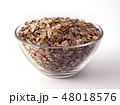 oat flakes in a glass bowl on white backrgound 48018576