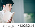 窓際で本を読む白いシャツの男性 48023214