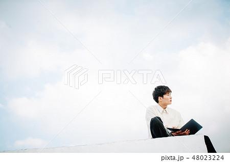 屋上に座ってノートパソコンを開く男性 48023224