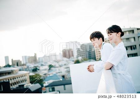屋上に並ぶ白衣を着た男女 48023513
