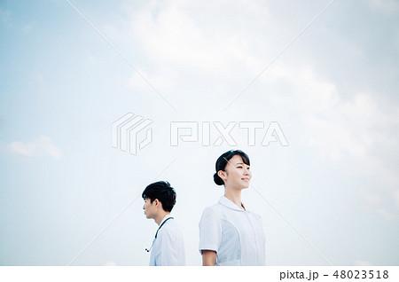 屋上に立つ白衣を着た背中合わせの男女 48023518
