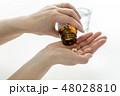 薬の瓶を左手で持ち上げて右手の手のひらに錠剤の薬を出すまでの一連の動作/白背景 48028810
