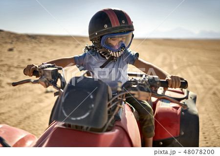 Kid in helmet and protect mask riding quad bike 48078200