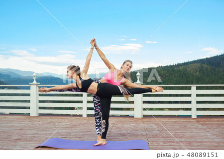 two women practicing half moon poseの写真素材 48089151  pixta