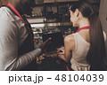 Barista man and woman looking at a laptop 48104039