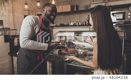 Male barista helps a girl to choose a dessert 48104238