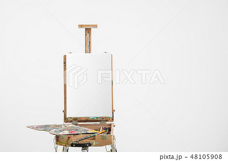 Artist easel with blank canvas on a white background. 48105908