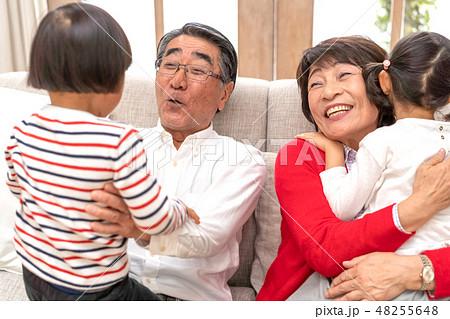 正月にじいちゃんばあちゃんに会いに実家に帰省し成長した孫を抱きしめて嬉しそうな祖父母 48255648