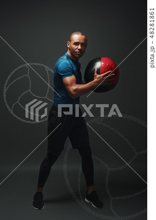 Training hard. Young sportsman standing over dark background with a ball in his hands 48281861