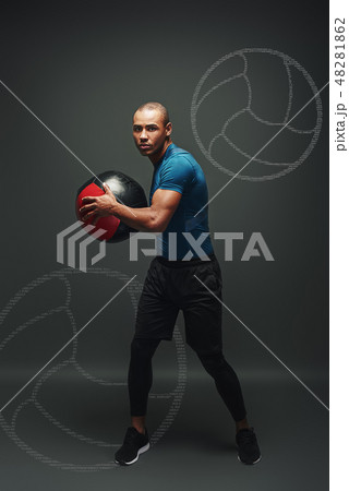 Respect the training. Young sportsman standing over dark background with a ball in his hands 48281862