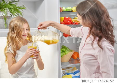 Young woman pouring orange, child holding glass. 48326157