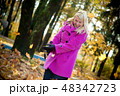 Young blonde woman in violet coat in park 48342723