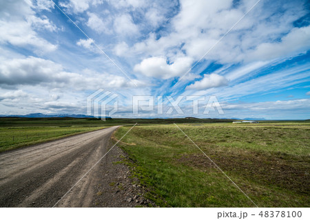Empty dirt road through countryside landscape. 48378100