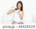 Smiling young Asian woman pours milk in a glass at home. 48426529