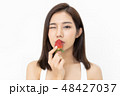 Portrait of a beautiful Asian girl kissing a fresh strawberry an 48427037
