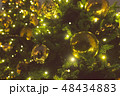 Christmas balls of gold color and garlands with bulbs on the branches of christmas tree, close-up 48434883