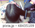 Hairdresser straights dark brown hair of beautiful woman using hair tongs in beauty salon. Back view 48435109