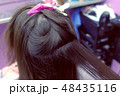 Hairdresser straights dark brown hair of woman using hair tongs in beauty salon. Hair close-up. 48435116