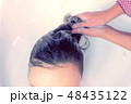 Barber washing client's hair in beauty salon in sink. 48435122