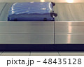 Baggage conveyor belt with blue suitcase at the airport, close-up side view. 48435128
