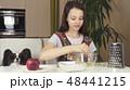 Teen girl with dog Papillon prepare cookies, knead the dough 48441215