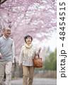 桜の中を歩くシニア夫婦 48454515