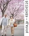 桜の中を歩くシニア夫婦 48454516