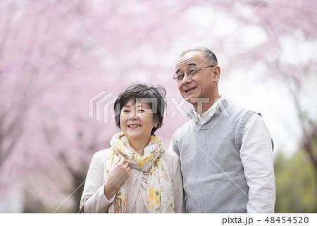 桜の中で微笑むシニア夫婦 48454520