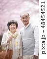 桜の中で微笑むシニア夫婦 48454521