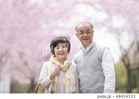 桜の中で微笑むシニア夫婦 48454523