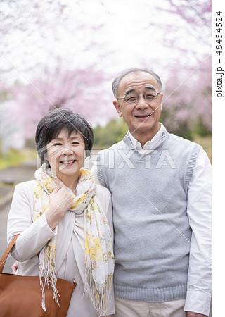 桜の中で微笑むシニア夫婦 48454524
