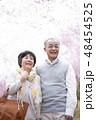 桜の中で微笑むシニア夫婦 48454525