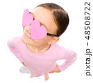 Little girl is holding hearts over her eyes 48508722