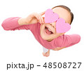 Little girl is holding hearts over her eyes 48508727