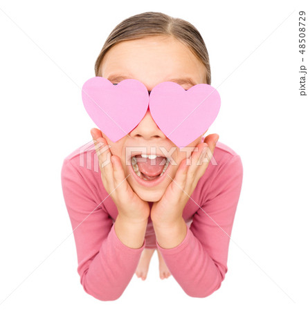 Little girl is holding hearts over her eyes 48508729