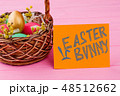 Woven basket filled with Easter eggs. 48512662