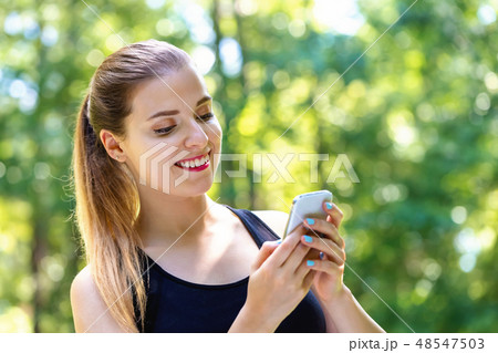 Young woman using her phone 48547503