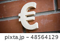 Wooden euro symbol on brick wall background 48564129