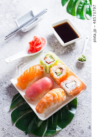 Various sushi on ceramic plate with metal Korean sticks on light stone background with green leaves 48573797