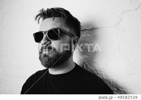 Portrait of a bearded serious man in sunglasses. 48582539