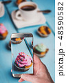 Man taking photo of Chocolate cupcake with cream 48590582