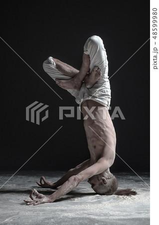 man standing in yoga shirshasana headstand poseの写真素材