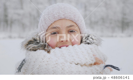 Many snowflakes fall on the face of a smiling girl in winter time 48606141