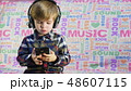 Cute small boy listening to the music in the black big headphones 48607115